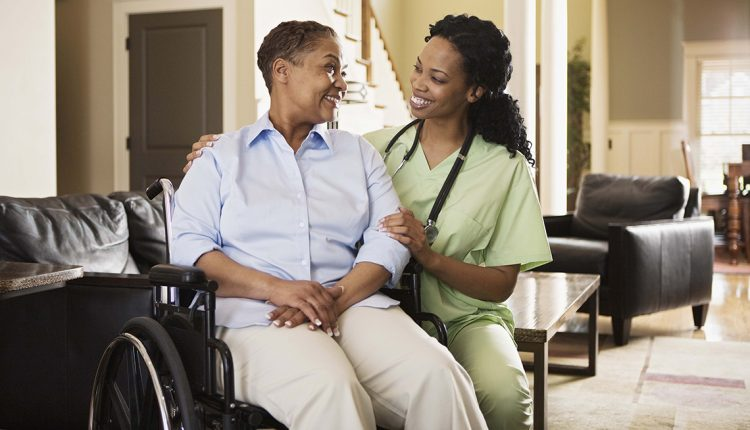 Nurse with woman in wheelchair at home